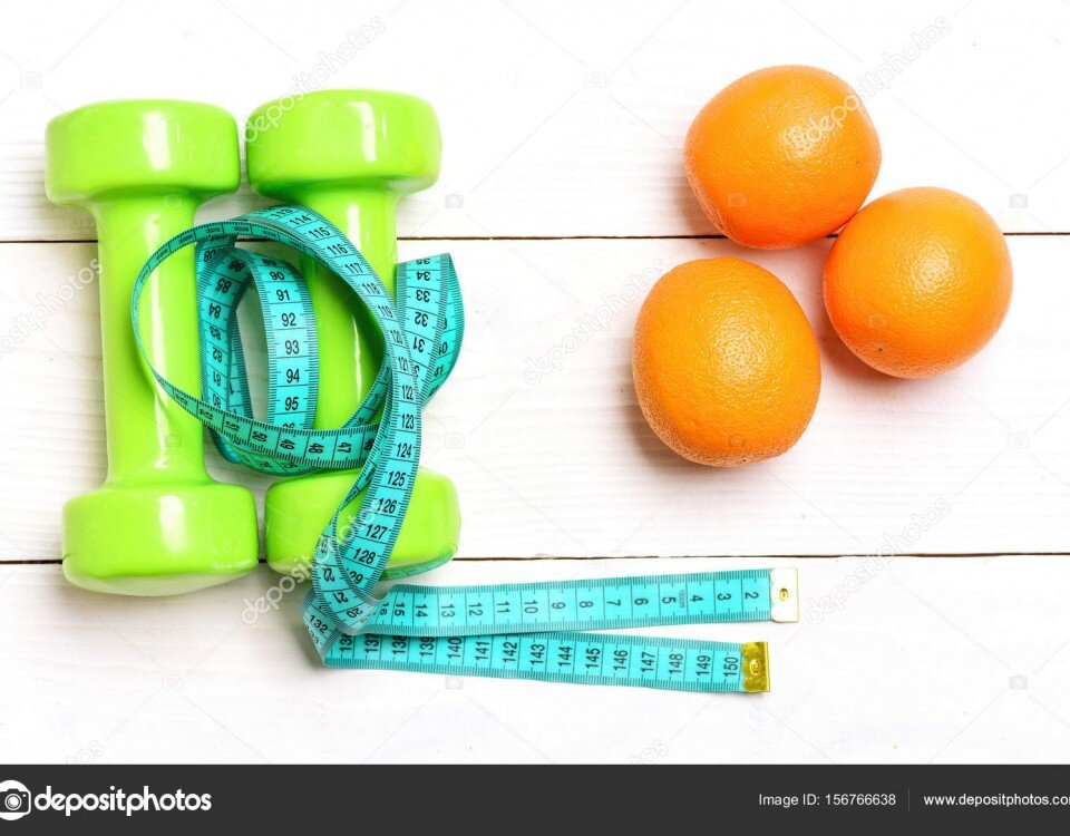 Oranges, dumbbells and cyan measuring tape lying on white wooden background, top view. Healthy nutrition, sport and diet concept